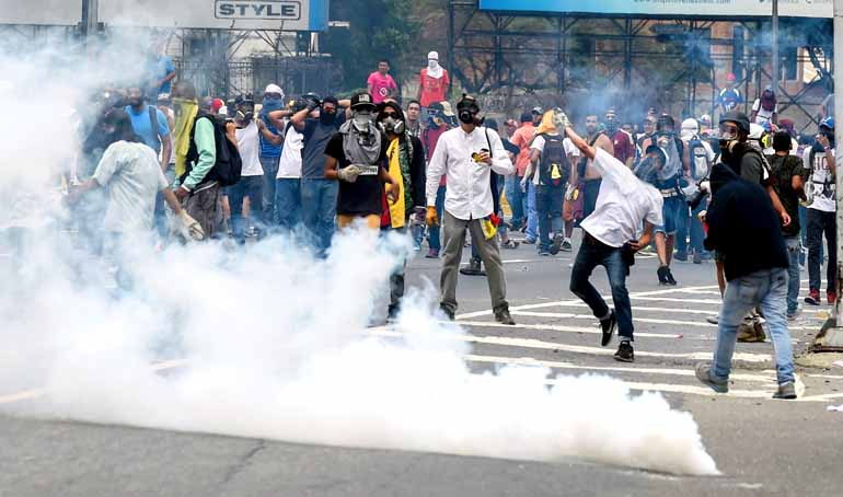 Juan Barreto/AFP - Policiais e manifestantes se enfrentaram em uma intensa troca de bombas de gás lacrimogêneo, pedras e coquetéis molotov em Caracas