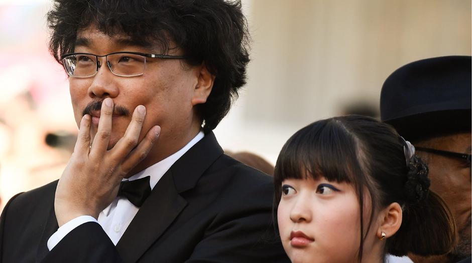 Anne Christine Poujout/AFP - O diretor sul-coreano Bong Joon-ho e a atriz Ah-Seo-hyun na exibição de 'Okja' que estreou entre vaias e apausos