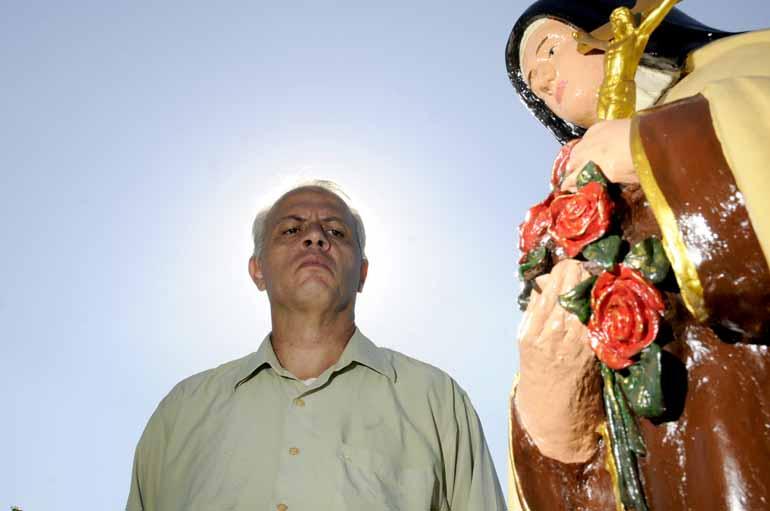 Saulo Ohara - Alexandre Achiropita com uma das estátuas religiosas restauradas por ele no Cemitério São Pedro, em Londrina
