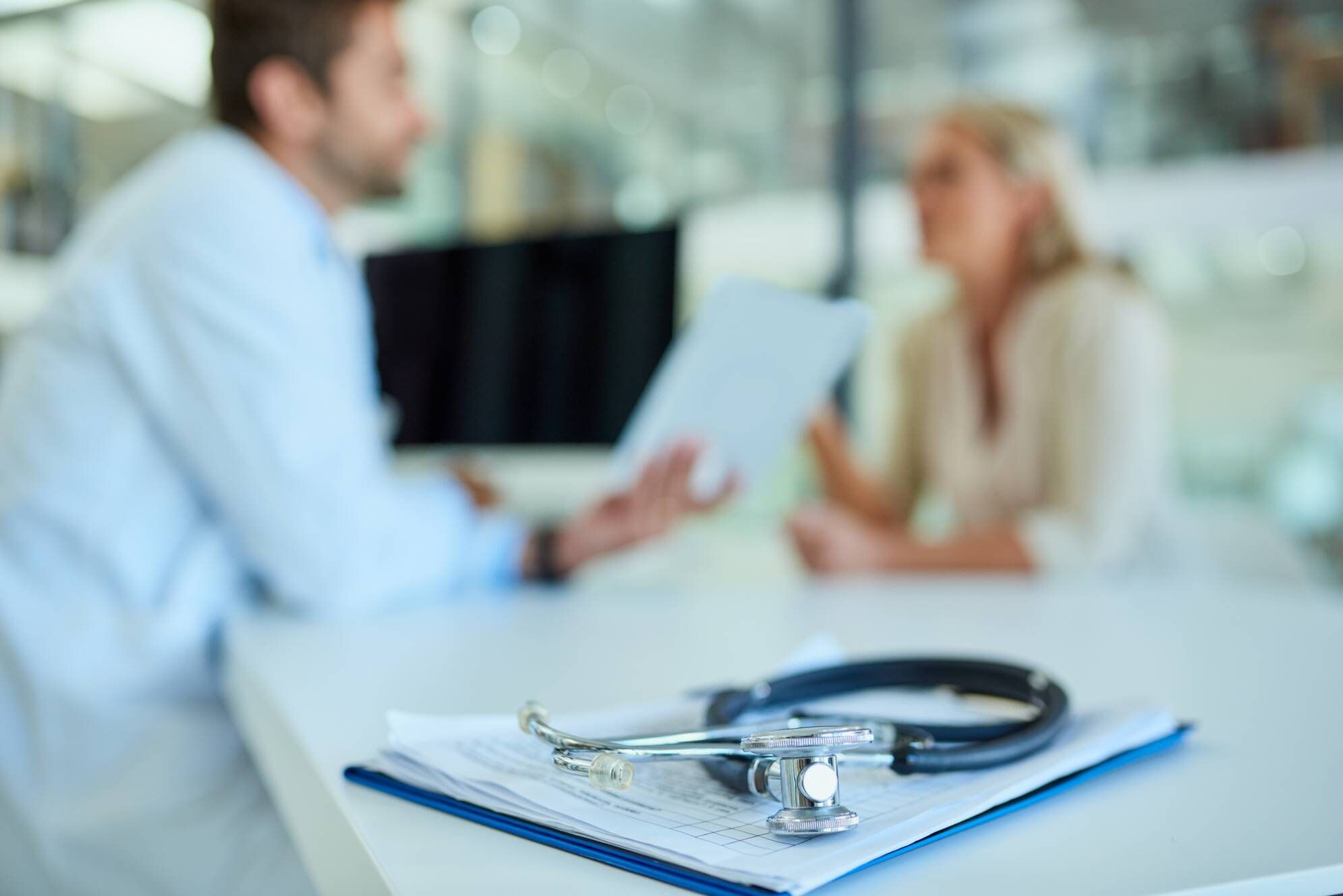 Foto de un estetoscopio y un portapapeles en un escritorio con un médico y un paciente en el fondo